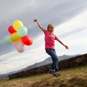 Little girl holding balloons out in the countryside